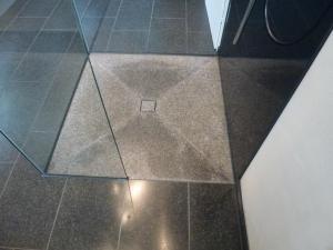 4.07-Granit-am-Boden-Ablauf-durch-Fuge-am-mittleren-Stein.-Glas-Rückwand-mit-Siebdruck-Anthrazit-und-Pflegeleichter-Duschwand